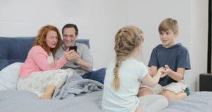 Το παιχνίδι αδελφών και αδελφών μαζί πέρα από τους γονείς χρησιμοποιεί την έξυπνη τηλεφωνική συνεδρίαση κυττάρων στην οικογένεια  απόθεμα βίντεο