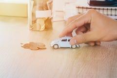 Το παιχνίδι αυτοκινήτων στο χέρι ατόμων στο γραφείο με το νόμισμα χρημάτων στην αποταμίευση τραπεζών βάζων, θερμό φίλτρο τόνου Στοκ εικόνα με δικαίωμα ελεύθερης χρήσης