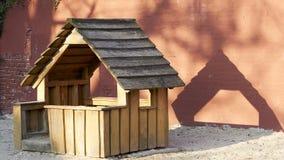 Το παιχνίδι κατοικεί στο Sandbox μπροστά από τον κόκκινο τοίχο στοκ εικόνα με δικαίωμα ελεύθερης χρήσης