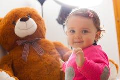 Το παιχνίδι κοριτσάκι μικρών παιδιών με μεγάλο teddy αντέχει Στοκ Φωτογραφίες