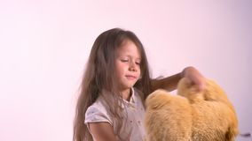 Το παιχνίδι παιδάκι με το βελούδο teddy αντέχουν και ο χορός, κρατώντας το παιχνίδι, στάση που απομονώνεται στο ρόδινο υπόβαθρο σ απόθεμα βίντεο