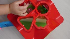 Το παιχνίδι παιδιών σε ένα σπίτι παιχνιδιών με τις τρύπες και ρίχνει απόθεμα βίντεο