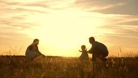 Το παιχνίδι Mom και μπαμπάδων με το παιδί στο πάρκο στο ηλιοβασίλεμα, παιδί λαμβάνει τα πρώτα μέτρα ευτυχής λίγη κόρη που παίζει  απόθεμα βίντεο