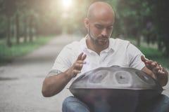 Το παιχνίδι ατόμων κρεμά τη συνεδρίαση ν τυμπάνων το πάρκο Στοκ Εικόνες
