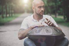 Το παιχνίδι ατόμων κρεμά τη συνεδρίαση ν τυμπάνων το πάρκο Στοκ Φωτογραφία