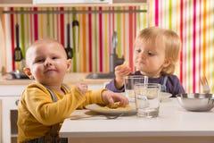 Το παιχνίδι αδελφών και αδελφών οικογενειακών μωρών τρώει το γεύμα στην κουζίνα παιχνιδιών Στοκ Εικόνες