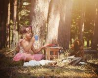 Το παιχνίδι κοριτσιών νεράιδων με Teddy αντέχει στα ξύλα στοκ εικόνες