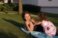 Το παιχνίδι μικρών κοριτσιών με τη μητέρα της Στοκ Εικόνες