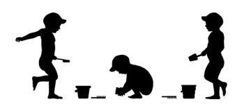 Το παιχνίδι μικρών παιδιών στις σκιαγραφίες παραλιών έθεσε 1 Στοκ Εικόνα
