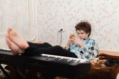 Το παιχνίδι σε ένα κινητό τηλέφωνο είναι πιό ενδιαφέρον, απ'ό, τι στο πιάνο στοκ εικόνες