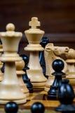 Το παιχνίδι σκακιού, κλείνει επάνω ενός λευκού βασιλιά, άλλοι αριθμοί στο μέτωπο Στοκ Φωτογραφία