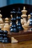 Το παιχνίδι σκακιού, κλείνει επάνω ενός μαύρων βασιλιά και μιας βασίλισσας, άλλοι αριθμοί στο μέτωπο Στοκ φωτογραφία με δικαίωμα ελεύθερης χρήσης