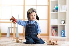 Το παιδί έντυσε όπως τα πειραματικά παιχνίδια αεροπόρων με τα αεροπλάνα παιχνιδιών στο σπίτι στο δωμάτιό του Στοκ φωτογραφία με δικαίωμα ελεύθερης χρήσης