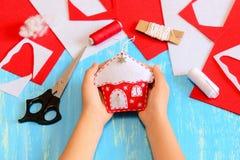 Το παιδί έραψε μια αισθητή διακόσμηση σπιτιών χριστουγεννιάτικων δέντρων Το παιδί κρατά τη διακόσμηση σπιτιών Χριστουγέννων στα χ Στοκ Εικόνες