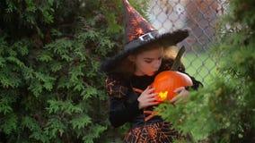 Το παιδί λίγη μάγισσα σε αποκριές σε ένα υπόβαθρο του φθινοπώρου φεύγει, κολοκύθα εκμετάλλευσης κοριτσιών με ένα καίγοντας κερί κ απόθεμα βίντεο