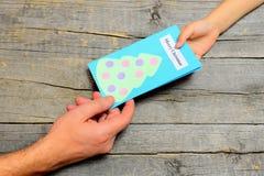 Το παιδί δίνει μια κάρτα Χριστουγέννων στον μπαμπά Λίγο παιδί δίνει ένα δώρο στον πατέρα Τα παιδιά δίνουν και χέρι ατόμων Κάρτα Κ Στοκ εικόνα με δικαίωμα ελεύθερης χρήσης
