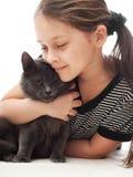 Το παιδί αγκαλιάζει ήπια τη γάτα στοκ φωτογραφίες