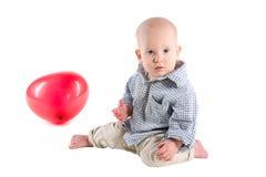 Το παιδί αγοριών είναι σε ένα πουκάμισο καρό, ένα κόκκινο μπαλόνι Στοκ εικόνα με δικαίωμα ελεύθερης χρήσης