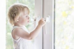 Το παιδί ανοίγει το παράθυρο Μικρό κορίτσι στο παράθυρο Στοκ εικόνες με δικαίωμα ελεύθερης χρήσης