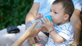 Το παιδί αποσβήνει τη δίψα με το νερό από ένα μπουκάλι απόθεμα βίντεο