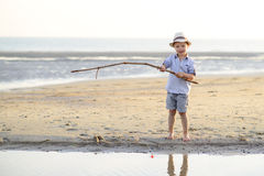 Το παιδί αλιεύει στην παραλία στην παραλία Στοκ Φωτογραφίες