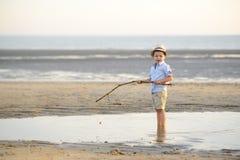 Το παιδί αλιεύει στην παραλία στην παραλία Στοκ Εικόνα