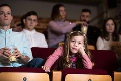 Το παιδί είναι βαριεστημένο στον κινηματογράφο Στοκ εικόνες με δικαίωμα ελεύθερης χρήσης