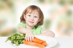 Το παιδί θέλει να φάει τα καρότα στοκ εικόνα
