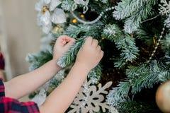 Το παιδί διακοσμεί ένα χριστουγεννιάτικο δέντρο στοκ φωτογραφίες