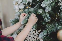Το παιδί διακοσμεί ένα χριστουγεννιάτικο δέντρο στοκ εικόνα