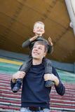 Το παιδί κάθεται στους ώμους του μπαμπά του και φαίνεται ευτυχές Στοκ εικόνες με δικαίωμα ελεύθερης χρήσης
