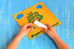 Το παιδί κάνει ένα σχισμένο δέντρο εγγράφου Το παιδί κρατά στα χέρια του ένα κομμάτι Πράσινης Βίβλου και το κολλά Τέχνη εγγράφου  Στοκ Εικόνες