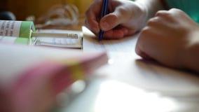 Το παιδί κάνει την εργασία του, γράφει σε ένα copybook στην επιτραπέζια κινηματογράφηση σε πρώτο πλάνο απόθεμα βίντεο
