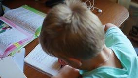 Το παιδί κάνει την εργασία του, γράφει σε ένα copybook στον πίνακα φιλμ μικρού μήκους