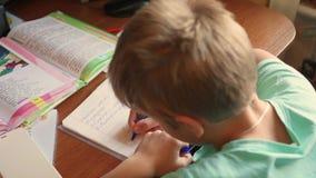 Το παιδί κάνει την εργασία του, γράφει σε ένα copybook στον πίνακα απόθεμα βίντεο