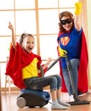 Το παιδί και η μητέρα έντυσαν ως superheroes χρησιμοποίηση της ηλεκτρικής σκούπας στο δωμάτιο Οικογένεια - η γυναίκα και η κόρη π στοκ εικόνες