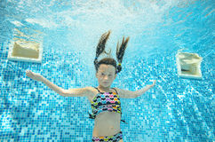 Το παιδί κολυμπά στη λίμνη υποβρύχια, το ευτυχές ενεργό κορίτσι βουτά και έχει τη διασκέδαση κάτω από το νερό, αθλητισμός παιδιών Στοκ Εικόνες