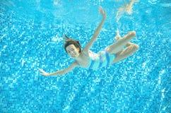 Το παιδί κολυμπά στη λίμνη υποβρύχια, το ευτυχές ενεργό κορίτσι βουτά και έχει τη διασκέδαση κάτω από το νερό, αθλητισμός παιδιών Στοκ εικόνες με δικαίωμα ελεύθερης χρήσης