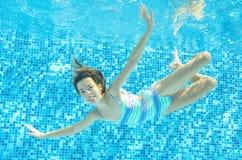 Το παιδί κολυμπά στη λίμνη υποβρύχια, το ευτυχές ενεργό κορίτσι βουτά και έχει τη διασκέδαση κάτω από το νερό, αθλητισμός παιδιών Στοκ Φωτογραφίες