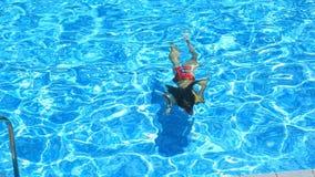 Το παιδί κολυμπά στο μπλε νερό της λίμνης επάνω από την όψη Το κορίτσι βουτά κάτω από το νερό στη λίμνη απόθεμα βίντεο