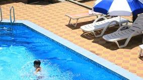 Το παιδί κολυμπά στο μπλε νερό της λίμνης επάνω από την όψη φιλμ μικρού μήκους