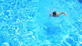 Το παιδί κολυμπά στο μπλε νερό της λίμνης επάνω από την όψη απόθεμα βίντεο
