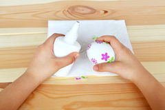 Το παιδί κρατά ένα αυγό Πάσχας decoupage και μια κόλλα Στοκ Εικόνα