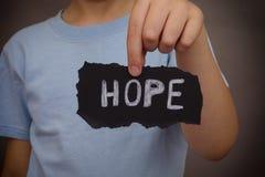 Το παιδί κρατά το κομμάτι του μαύρου χαρτί με την ελπίδα λέξης στοκ εικόνες