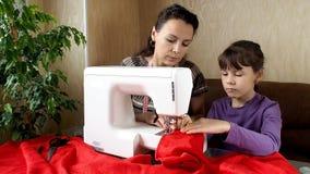 Το παιδί μαθαίνει να ράβει στη ράβοντας μηχανή απόθεμα βίντεο