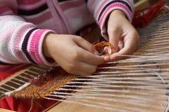 το παιδί μαθαίνει να υφαίν&epsi Στοκ Εικόνα