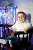 Το παιδί με ένα άσπρο πουλόβερ κάθεται σε μια καρέκλα δίπλα σε έναν κλάδο χριστουγεννιάτικων δέντρων στο χαμόγελο στοκ εικόνες