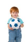 Το παιδί με την κόκκινος-τρίχα κρατά ένα soccerball διαθέσιμο Στοκ Εικόνα