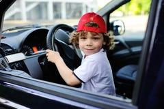 Το παιδί με τη σγουρή τρίχα και μια κόκκινη ΚΑΠ κάθεται πίσω από τη ρόδα του αυτοκινήτου Στοκ Εικόνες
