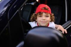Το παιδί με τη σγουρή τρίχα και μια κόκκινη ΚΑΠ κάθεται πίσω από τη ρόδα του αυτοκινήτου Στοκ εικόνες με δικαίωμα ελεύθερης χρήσης